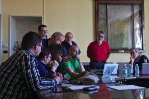 Project partners gather round to look at a notebook screen where the latest version of the visualisation platform is shown.